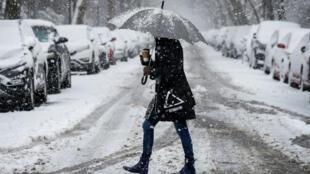 Una mujer camina durante una tormenta de nieve en Brooklyn, Nueva York, el 21 de marzo de 2018.