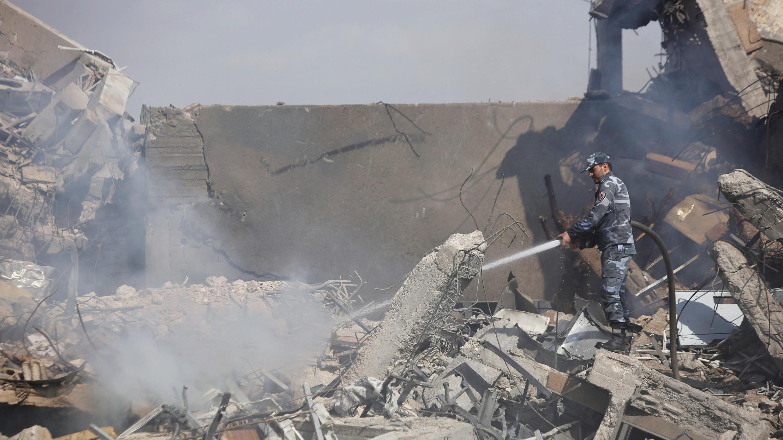 Un bombero sirio en el un centro de investigación científica  destruido en los bombardeos en Damasco, Siria, el 14 de abril de 2018.