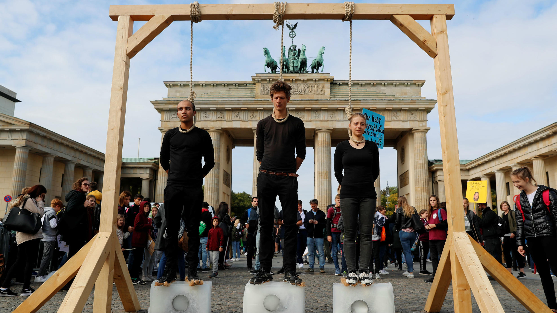 Activistas se paran en bloques de hielo bajo una improvisada horca mientras participan en la huelga climática global del movimiento Viernes para el Futuro, frente a la Puerta de Brandenburgo en Berlín, Alemania, el 20 de septiembre de 2019.