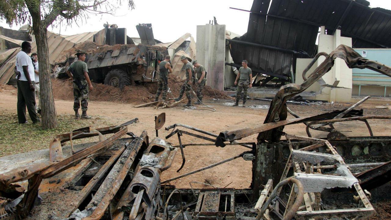 Des soldats français nettoient les débris autour d'un véhicule blindé détruit au lycée Descartes de Bouaké qui servait de camp militaire, le 10 novembre 2004.