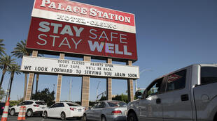 People wait in their cars for food donations outside the Palace Station hotel and casino on May 7 in Las Vegas