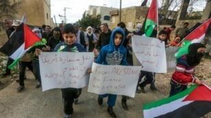 أطفال يشاركون في تظاهرة منددة بخطط ترامب المتعلقة بنقل السفارة الأمريكية للقدس، في بلدة كفر قدوم قرب نابلس في 13 كانون الثاني/يناير 2017