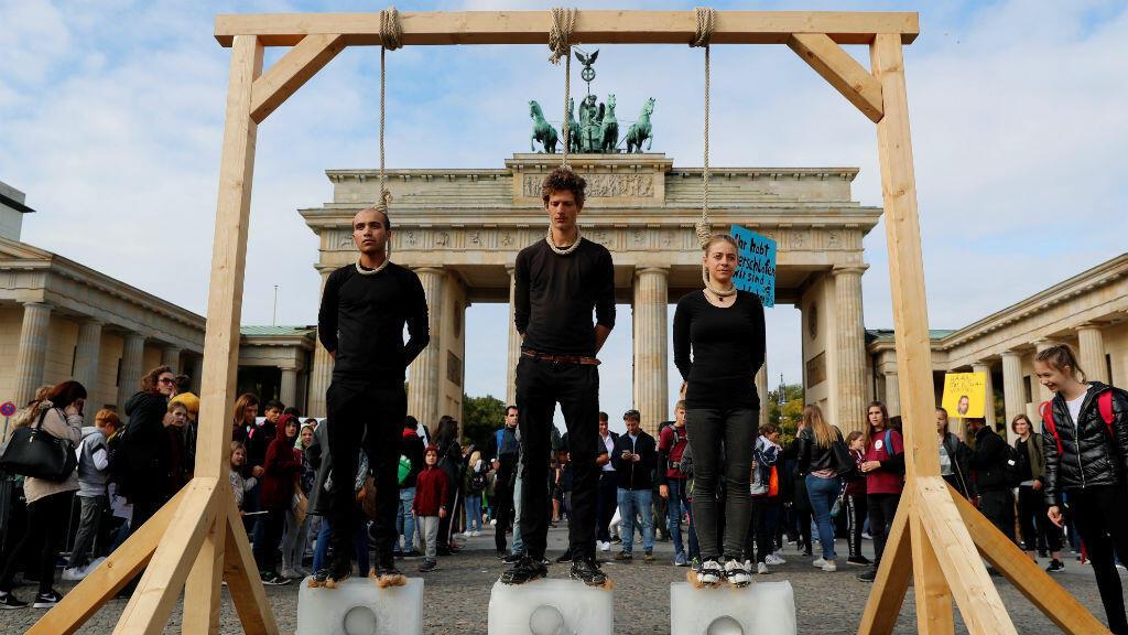 Activistas se manifiestan frente a la Puerta de Brandemburgo con sogas al cuello y subidos a bloques de hielo, durante la huelga global por el clima. Berlín, Alemania, 20 de septiembre de 2019.