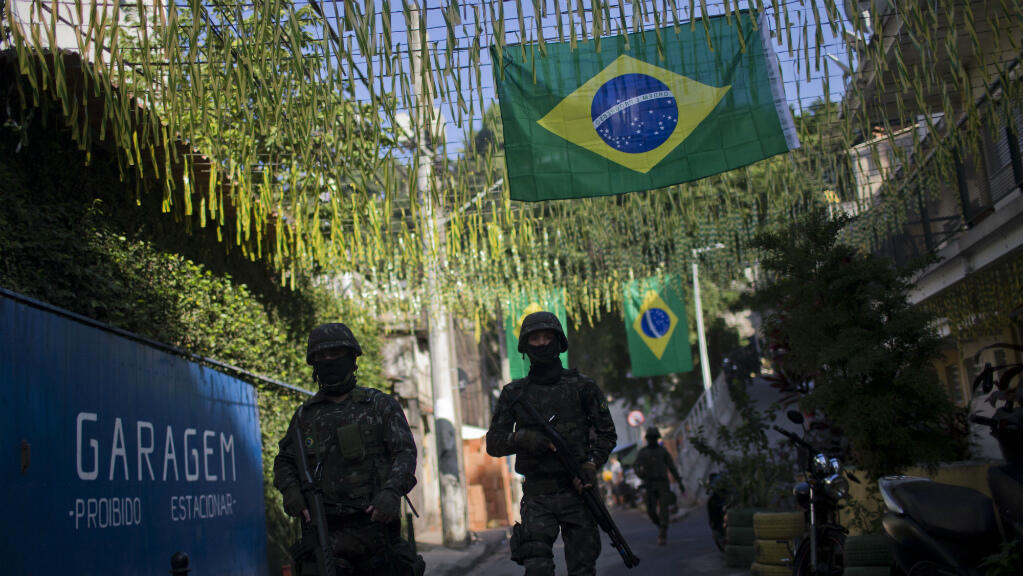Des membres de l'armée brésilienne patrouillent lors d'une opération à l'intérieur des favelas à Rio de Janeiro, au Brésil, le 21 juin 2018.