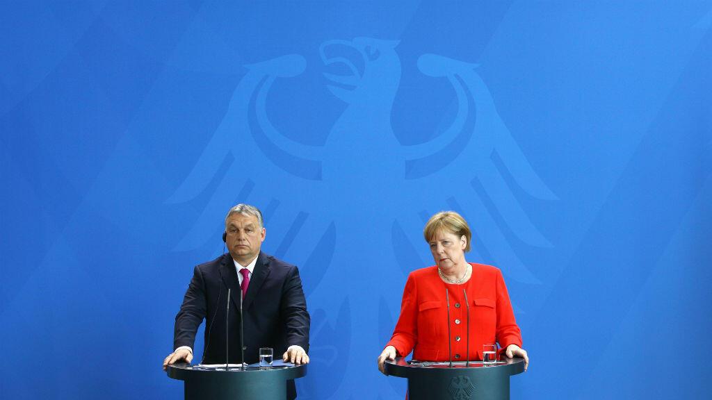 المستشارة الألمانية أنغيلا ميركل ورئيس الوزراء المجري فيكتور أوربان في مؤتمر صحفي بعد اجتماعهما في برلين، 5 تموز/يوليو 2018.