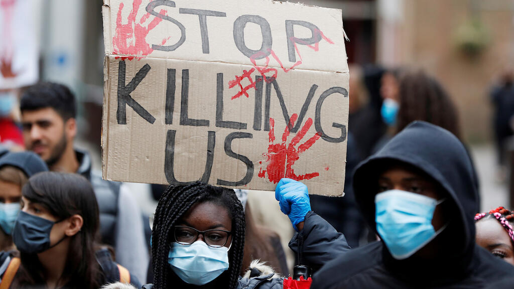 A demonstrator wears a protective face mask holds a placard during a Black Lives Matter protest in Watford, following the death of George Floyd who died in police custody in Minneapolis, Watford, Britain, June 6, 2020.