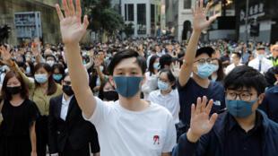 Des manifestants lèvent les mains lors d'une protestation dans le quartier central à Hong Kong, le 15 novembre 2019.