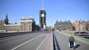 Un peatón cruza el Puente de Westminster de Londres, con el parlamento de fondo, el 24 de marzo de 2020