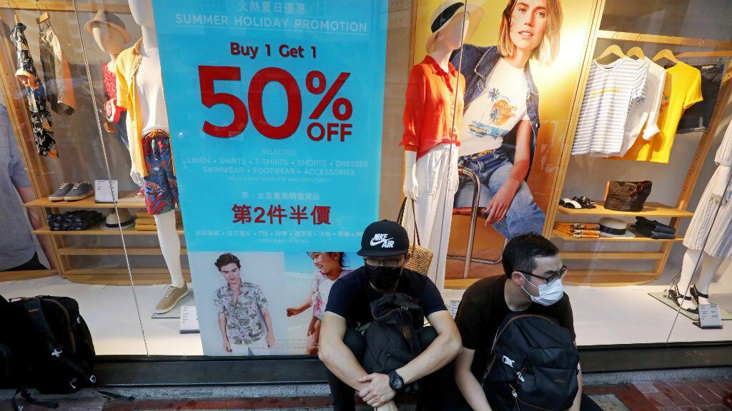 Personas se sientan al lado de una tienda durante una jornada de protestas antigubernamentales en Hong Kong, China, el 17 de agosto de 2019.