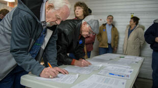 Attendees sign in as they arrive at a Democratic Party caucus in Keokuk, Iowa, on February 1, 2020.