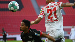 Le défenseur brésilien de Leverkusen, Wendell (g), et l'attaquant de Mayence, Karim Onisiwo, luttent pour le ballon lors du match de Bundesliga à Leverkusen, le 13 février 2021