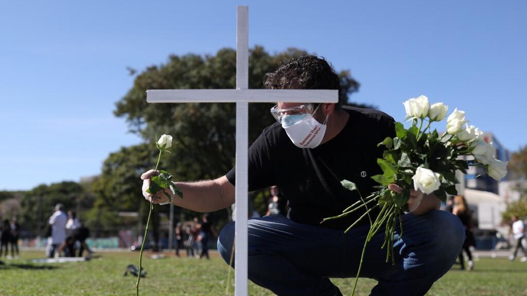 Un hombre coloca flores cerca de una cruz durante una protesta simbólica y homenaje a los trabajadores de la salud que murieron a causa de la enfermedad de coronavirus. En Sao Paulo, Brasil, el 20 de junio de 2020.