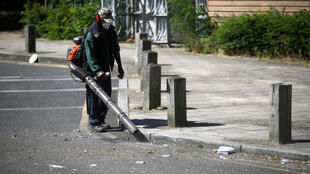 A worker cleans street in Brixton, London, June 25, 2020, after an illegal party resulted in police injuries.