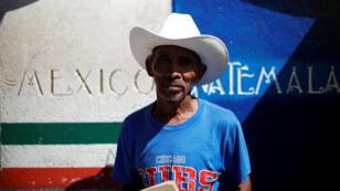 El migrante guatemalteco Esteban Lorenzo posa para una foto mientras espera con otros migrantes centroamericanos en un puente que conecta a Guatemala y México para cruzar a México, en Talisman, México, 23 de octubre de 2018.