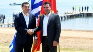 El primer ministro griego, Alexis Tsipras (izq), y su homólogo macedonio, Zoran Zaev, se dan la mano a orillas del lago Prespa, fronterizo entra ambos países, el pasado 17 de junio cerca de Otesevo (Macedonia)