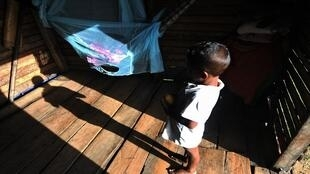 طفل من مسكيتو يشاهد شقيقه الرضيع في منزله في برامينيتارا، بويرتو لمبيرا، هندوراس - 8 يوليو/تموز 2019.