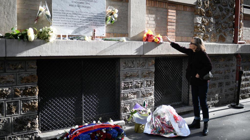 Une femme dépose un bouquet près de la plaque commémorative de l'attentat à la Belle Équipe, dans le 11e arrondissement de Paris, le 13 novembre 2017.