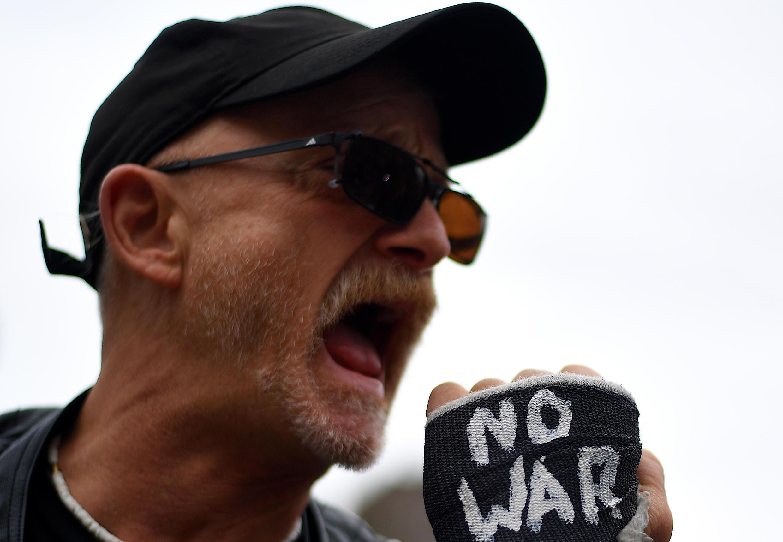 """Un manifestante con un brazo enyesado y un letrero que dice """"no guerra con Irán"""" asiste a una manifestación contra Trump el 11 de enero de 2020 en la ciudad de Nueva York."""