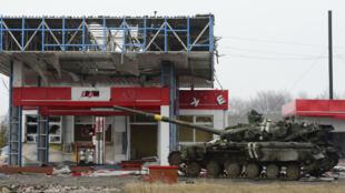 Un tank abandonné devant une station essence détruite durant des combats dans l'est de l'Ukraine, une image symbole des conséquences de la guerre sur l'économie.