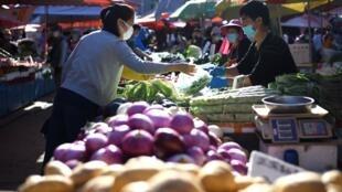 Una mujer con máscara facial compra verduras en un mercado de Pekín, el 12 de mayo de 2020
