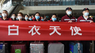 Medical workers from outside Wuhan stand behind a banner with their suitcases as they listen to a speech at the Wuhan Railway Station before leaving the epicentre of the novel coronavirus disease (COVID-19) outbreak, in Hubei province, China March 17, 2020. Picture taken March 17, 2020.