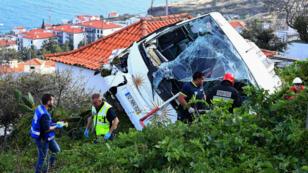 Bomberos junto a los restos del autobús turístico siniestrado en la isla de Madeira.