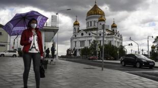 Una mujer con mascarilla pasa frente a la catedral del Cristo Salvador, en el centro de Moscú, el 14 de mayo de 2020