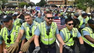 Un petit groupe de suprémacistes blancs emmené par Jason Kessler est escorté par la police sous les huées des anti-racistes, dimanche 12 août 2018 à Washington.