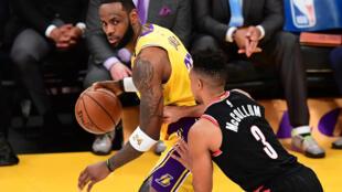 LeBron James, de Los Angeles Lakers, domina el balón ante CJ McCollum, de Portland Trailblazers, el 31 de enero de 2020 en partido de la NBA jugado en Los Angeles Lakers