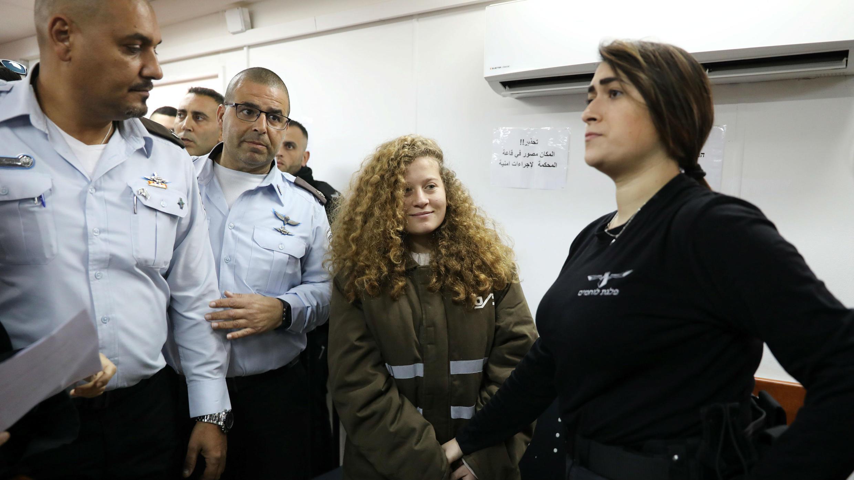 La adolescente palestina Ahed Tamimi ingresa a un tribunal militar escoltada por personal de seguridad israelí mientras su abogada Gaby Lasky (L) se encuentra cerca, en la Prisión de Ofer, cerca de la ciudad cisjordana de Ramallah, el 13 de febrero de 2018.