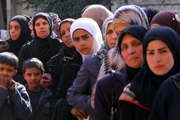 لاجئون فلسطينيون ينتظرون حصصا غذائية بمخيم اليرموك جنوب دمشق في 10 مارس 2015