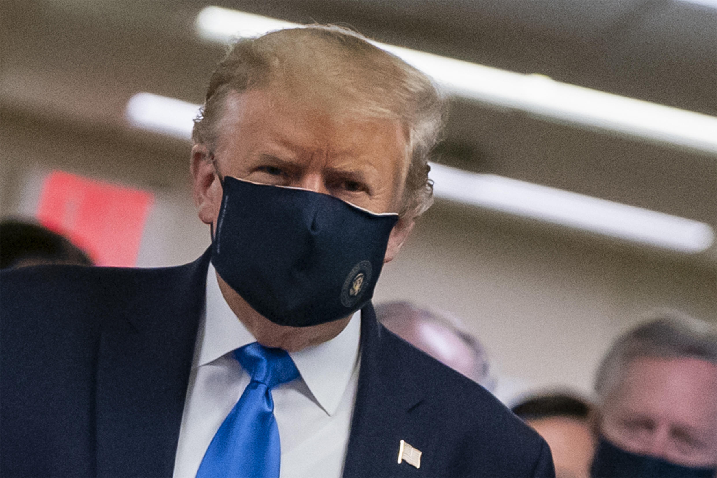 President Donald Trump makes a rare appearance in a mask as part of a new attempt to restore his standing with Americans over the handling of the coronavirus pandemic
