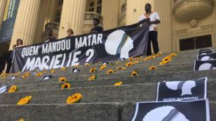 """Sur les escaliers de l'assemblée de l'État de Rio de Janeiro, des tournesols et des pancartes ont été déposés, jeudi 14 mars. Sur les affiches, on lit """"Qui a ordonné de tuer Marielle?"""""""