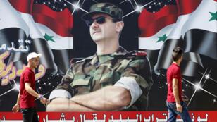 """Jóvenes sirios pasan frente a un cartel que muestra una foto del presidente Bashar al-Asad, en el centro de la capital, Damasco, el 9 de julio de 2018, con una leyenda debajo árabe que dice: """"Si el polvo del país habla, dirá Bashar al-Asad""""."""