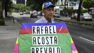 An opposition activist carries a kite with the name of recently deceased navy captain Rafael Acosta in Caracas: the US said it will impose snactions on the intelligence agency accused or torturing him to death