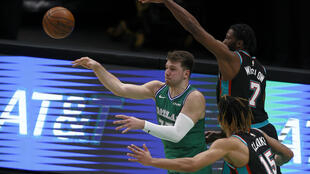 Dallas Mavericks star Luka Doncic passes the ball against Brandon Clarke, 15, and Justise Winslow ,7, of the Memphis Grizzlies in the second half at American Airlines Center