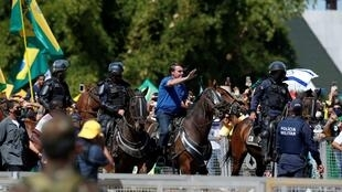 Brazil's President Jair Bolsonaro rides a horse during a meeting with supporters protesting in his favour, amid the coronavirus disease outbreak, in Brasilia, Brazil, on May 31, 2020.