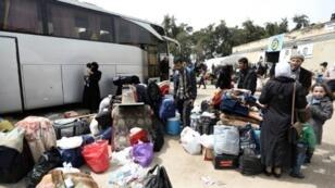 مدنيون سوريون ومقاتلون من المعارضة يصلون إلى قلعة المضيق بعد إجلائهم من الغوطة الشرقية في 28 آذار/مارس.