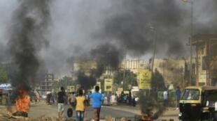 متظاهرون يحرقون إطارات السيارات في وسط شارع رئيسي في الخرطوم في 27 تموز/يوليو 2019 احتجاجا على نتائج التحقيق في فض اعتصام الخرطوم في يونيو/حزيران.