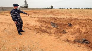 عضو من قوات الأمن التابعة لوزارة الداخلية في حكومة الوفاق الوطني الليبية يشير إلى موقع يشتبه في أنه مقبرة جماعية في ترهونة، في 11 حزيران/يونيو 2020.