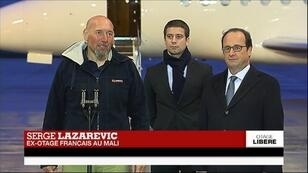Serge Lazarevic, Clément Verdon, le fils de l'otage exécuté Philippe Verdon, et François Hollande, sur le tarmac de l'aéroport de Villacoublay.