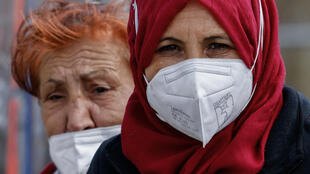 Two women wearing face masks are seen on April 2, 2021 in Berlin's Kreuzberg district, amid the ongoing coronavirus (Covid-19) pandemic.