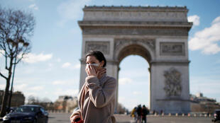 A woman wearing a protective mask walks near the Arc de Triomphe in Paris on March 15, 2020 following French Prime Minister Édouard Philippe's announcement to close non-indispensable businesses such as cafes, restaurants, cinemas, nightclubs and shops as France grapples with an outbreak of the novel coronavirus.