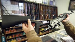 """Un """"bump stock"""" présenté près du fusil semi-automatique sur lequel il est possible de le monter."""