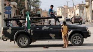 Un niño se encuentra en un camión montado con un arma en la ciudad fronteriza de Tal Abyad el 17 de octubre en Siria.