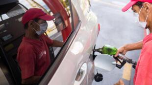 Un trabajador de una gasolinera despacha combustible con una máscara facial, en medio de la epidemia del coronavirus, el 23 de marzo de 2020 en Caracas