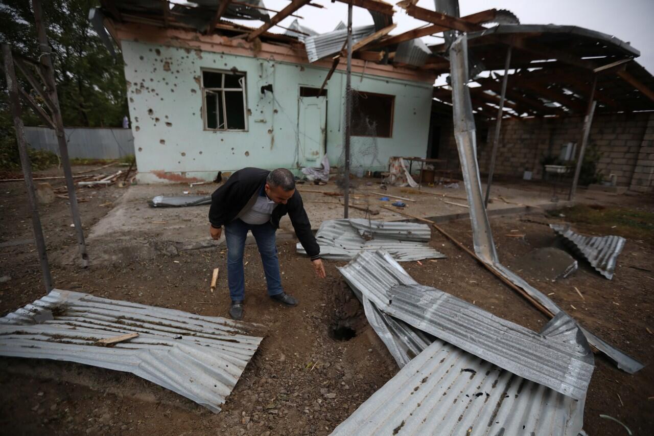 Un hombre señala un agujero de munición cerca de una casa dañada por los recientes bombardeos en la región separatista de Nagorno Karabaj. 1 de octubre de 2020.
