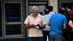 Greeks queue at an ATM in Athens amid restrictions of bank withdrawals on July 7, 2015