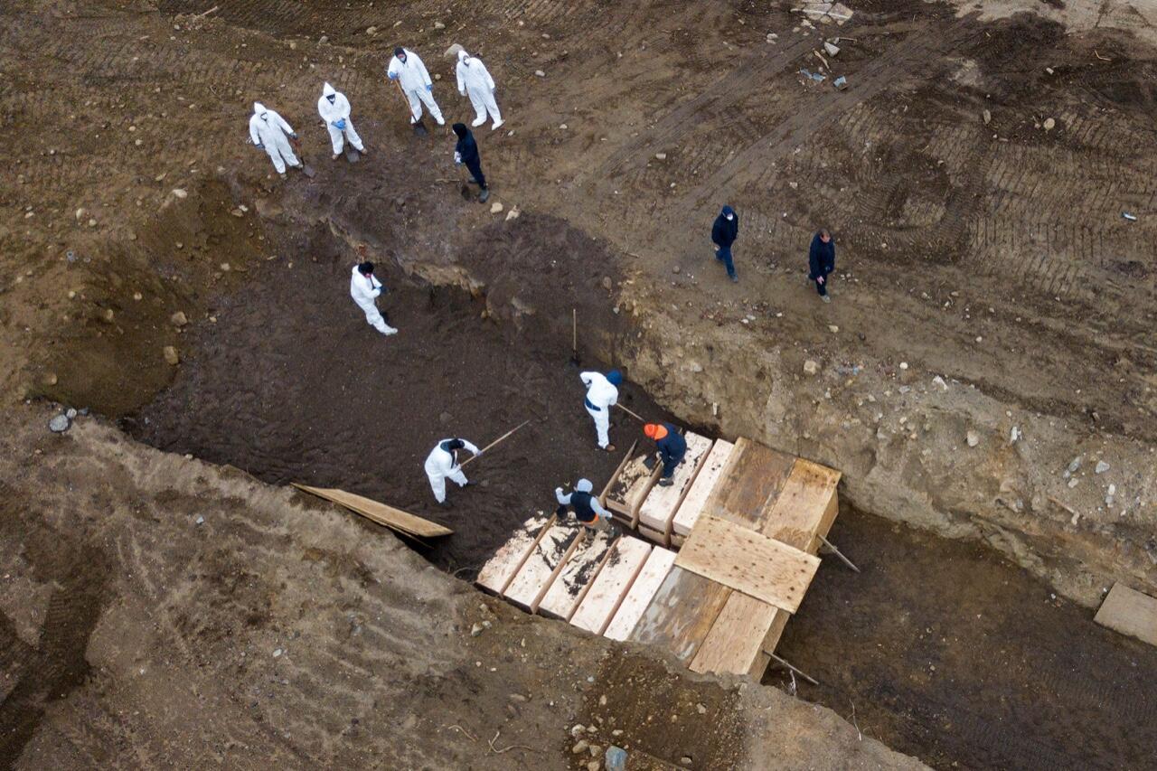 Integrantes del equipo de atención a la emergencia sanitaria por Covid-19 en Estados Unidos organizan cajas con cuerpos en la isla Hart de Nueva York el 9 de abril de 2020.