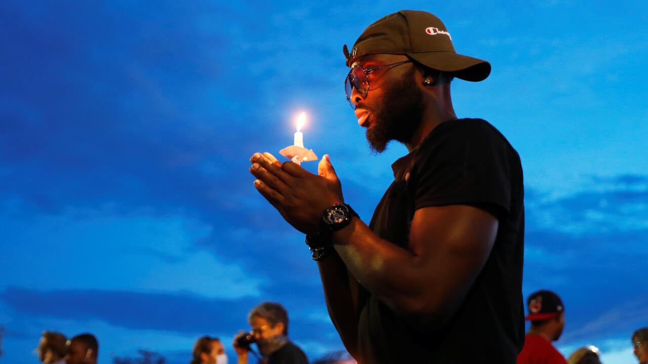 Un hombre sostiene una vela mientras reacciona en la escena de la muerte, bajo custodia policial de George Floyd en Minneapolis, Minnesota, EE. UU., el 3 de junio de 2020.